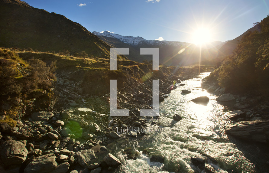 The sun shines bright on a lazy, trickling creek in the mountains at sunrise or sunset.
