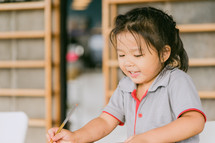 a little girl using colored pencils