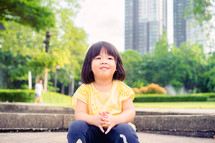 a toddler girl sitting in a park in a city