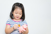 a little girl putting a coin in a piggy bank