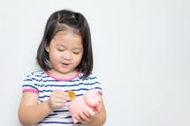 a little girl putting a coin in a piggy bank