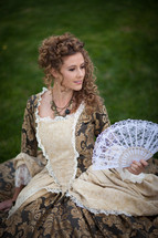 Woman in a Victorian dress with a lace fan sitting outside.