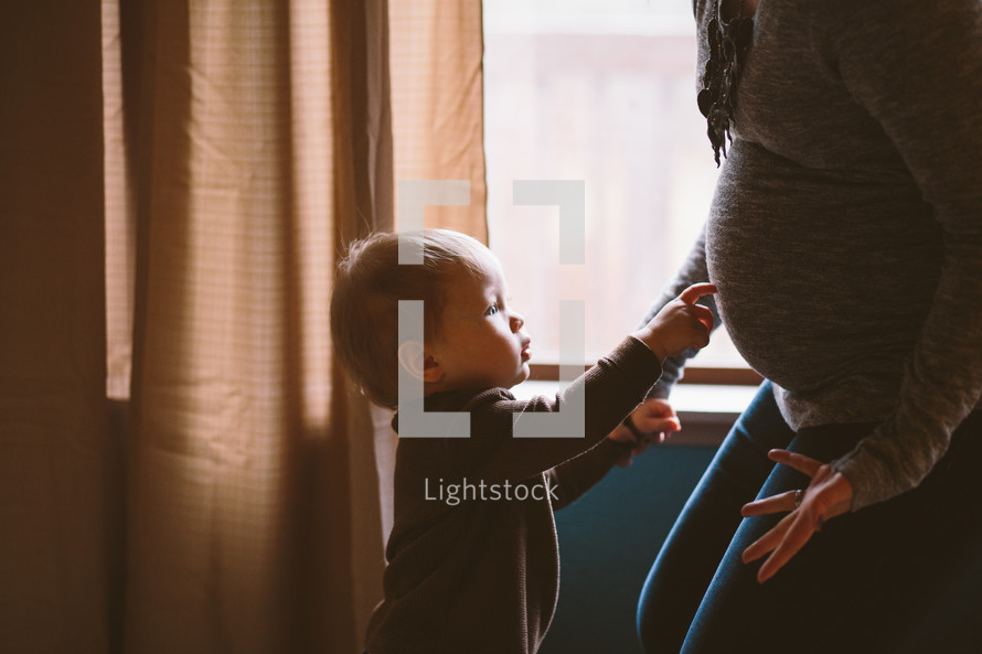 toddler boy pointing to his pregnant mother's belly