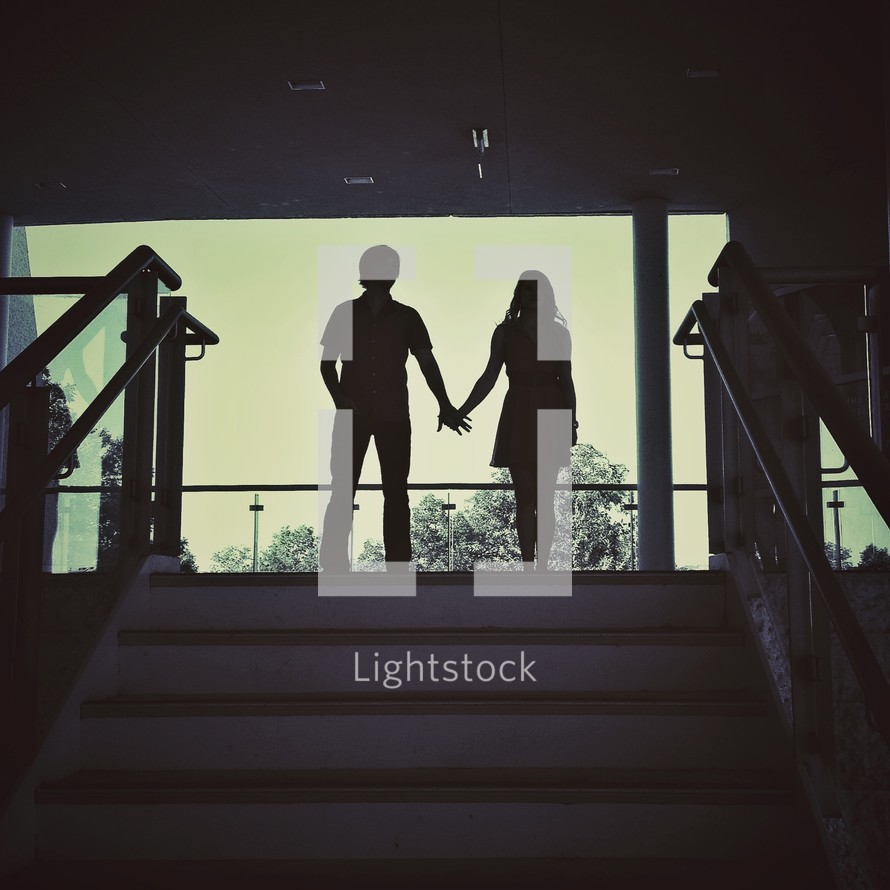 Silhouette of boy and girl holding hands at top of stair case.