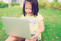 a little girl sitting in the grass with a laptop on her lap