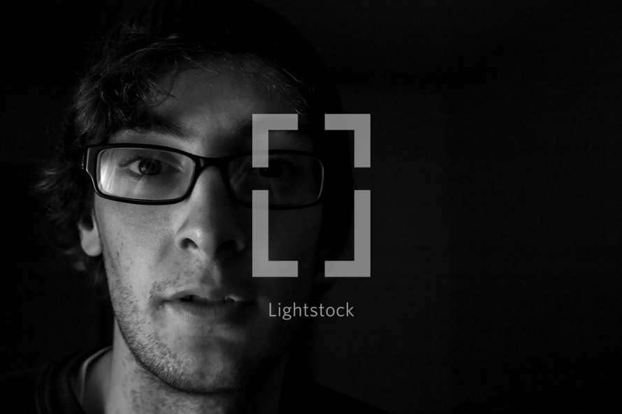 A man with glasses in the dark