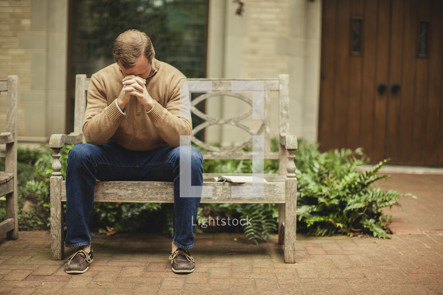 man with head bowed in prayer on a bench