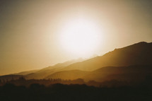 Sunrise behind a mountain.