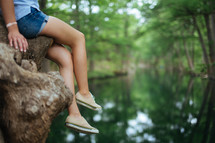 A girl in shorts dangles her legs from a tree over a river.