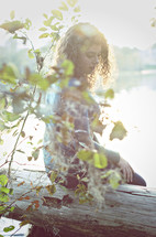 woman sitting on a fallen tree under the glow of sunlight