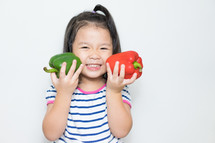 toddler girl holding peppers