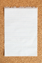 lined paper on a cork board