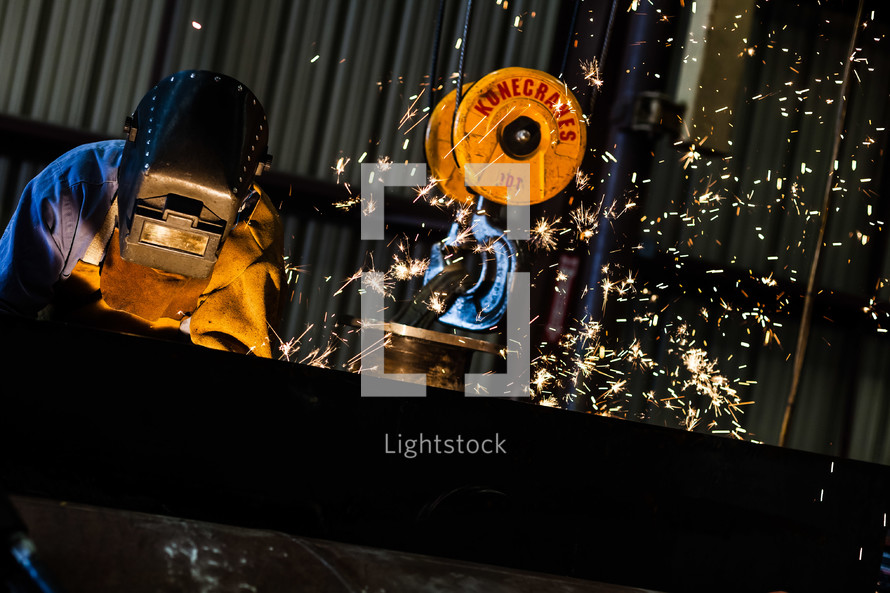 Sparks flying as Man welding welder hood mask industrial steel crane air arcing