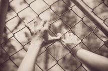 grasping hands on a chain link fence