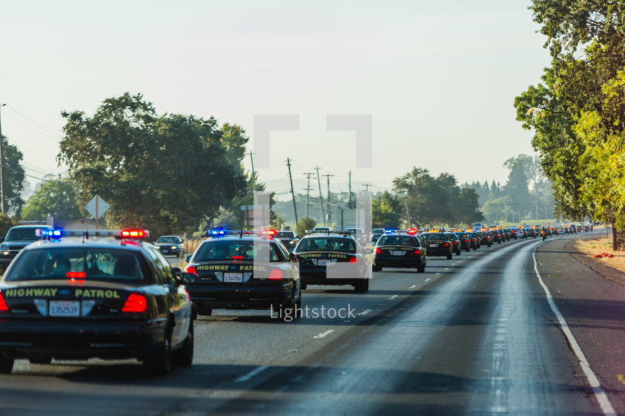 line of Highway patrol cars driving down freeway highway funeral procession