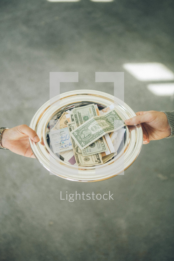 offering plate full of cash, checks, and envelopes