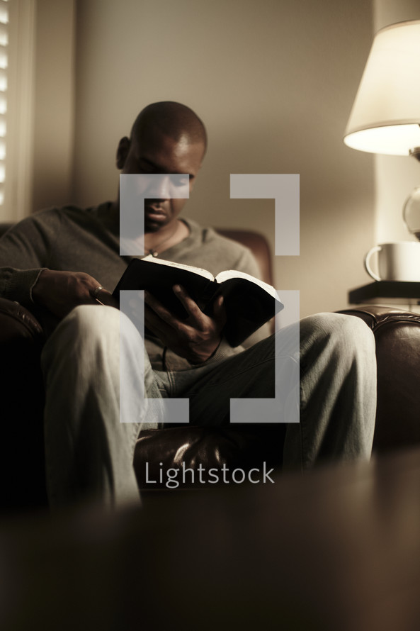 An African American man studying the Bible
