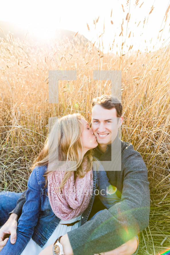 woman kissing a man on the cheek while sitting in a field