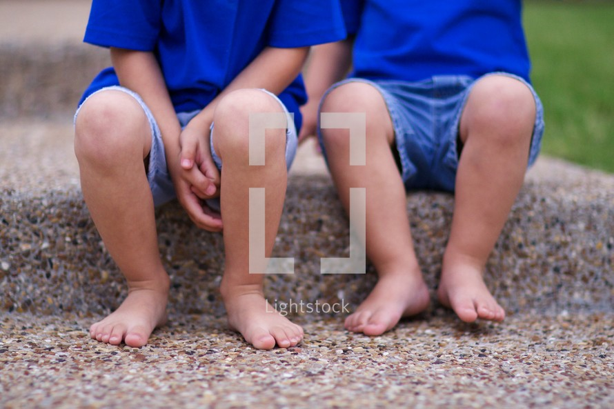 Two barefoot little boys sitting on a step