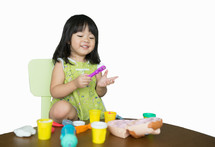 a toddler girl playing with play dough