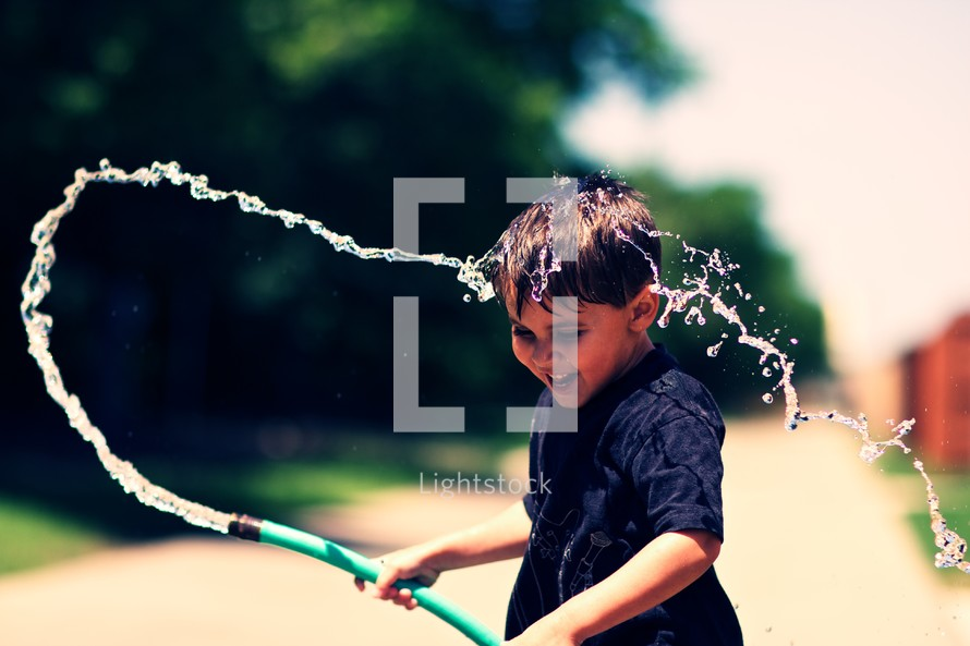 A young boy playing with a water hose