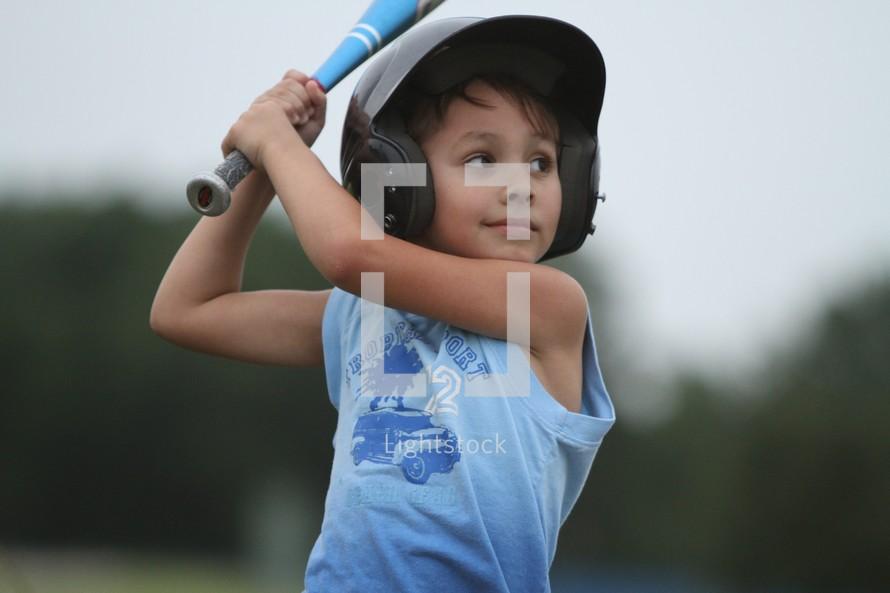 A boy ready to swing a baseball bat