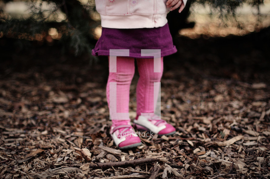 Toddler girl's leg standing in wood chips with tree and sunset in background.
