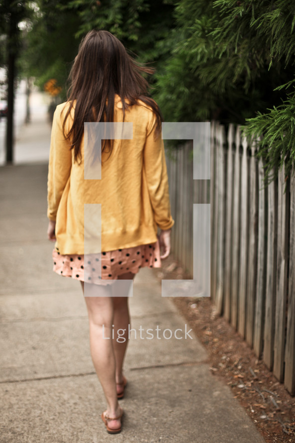 Woman walking down sidewalk
