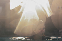 bright bokeh sunlight and a woman in a pool of water