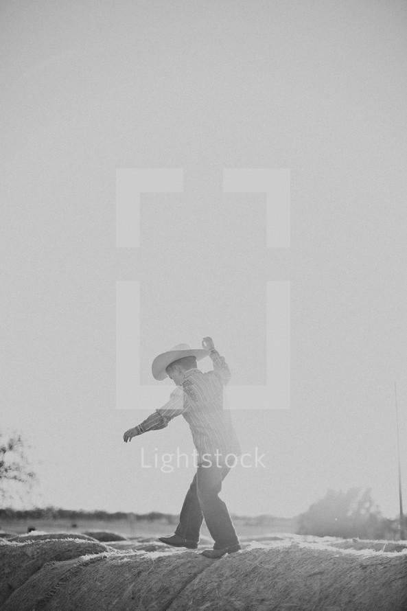 boy in a cowboy hat walking on hay bales