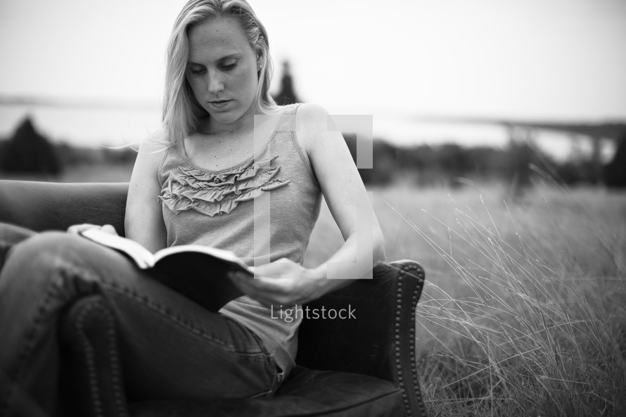 A girl sitting in a chair reading her Bible