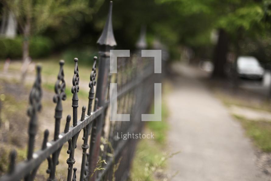 An iron fence lining a sidewalk.