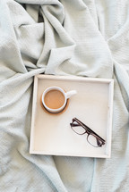 Eyeglasses and a cup of coffee in a square tray on a white cloth.