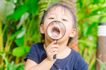a little girl holding a magnifying glass over her mouth