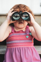 a child looking through binoculars