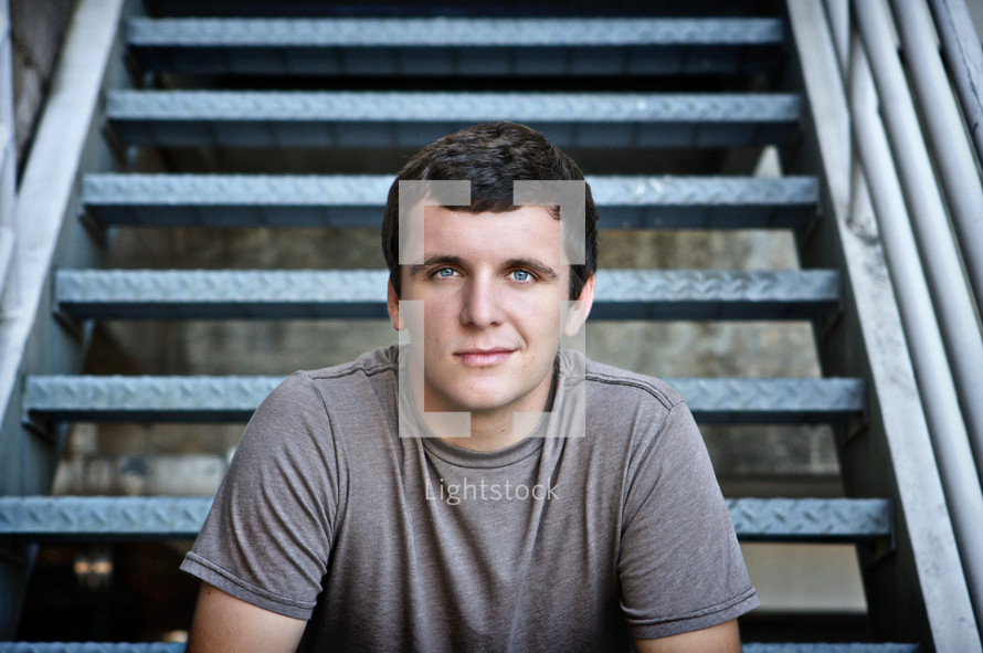 Smiling man sitting on staircase steps