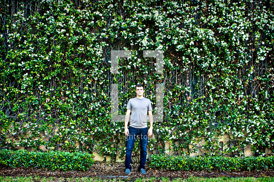 Man in front of wall made of wildflowers