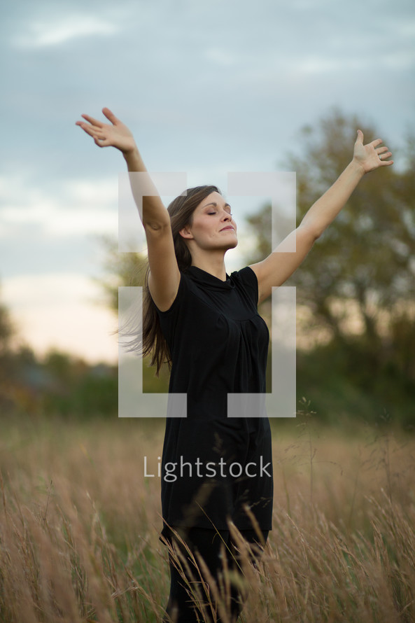 Woman with hands raised, in open field