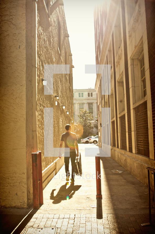 A man walking between two buildings.