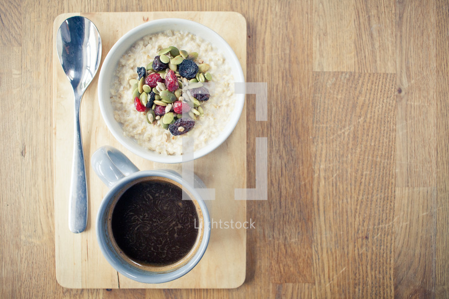 porridge with seeds and fruit and a coffee mug