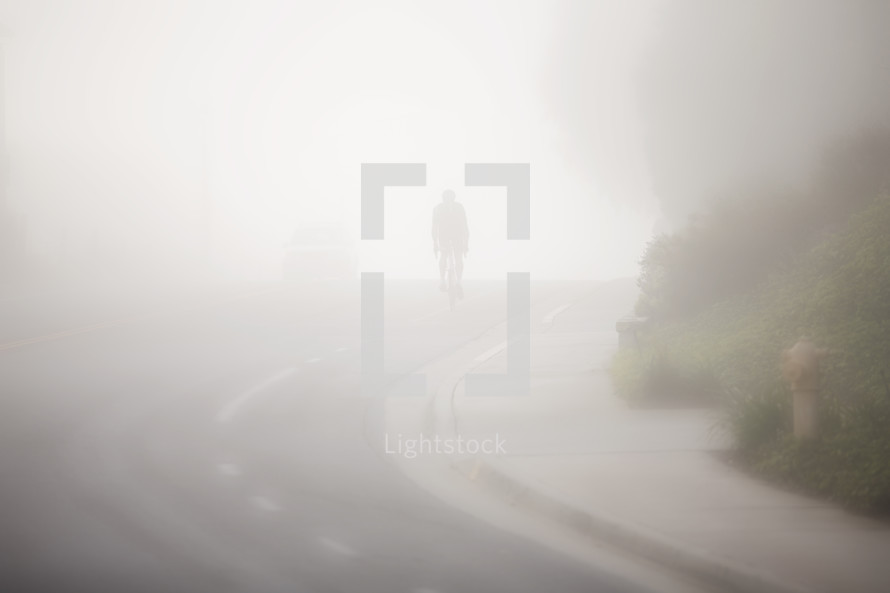 man riding a bike down a hill on a street under thick fog