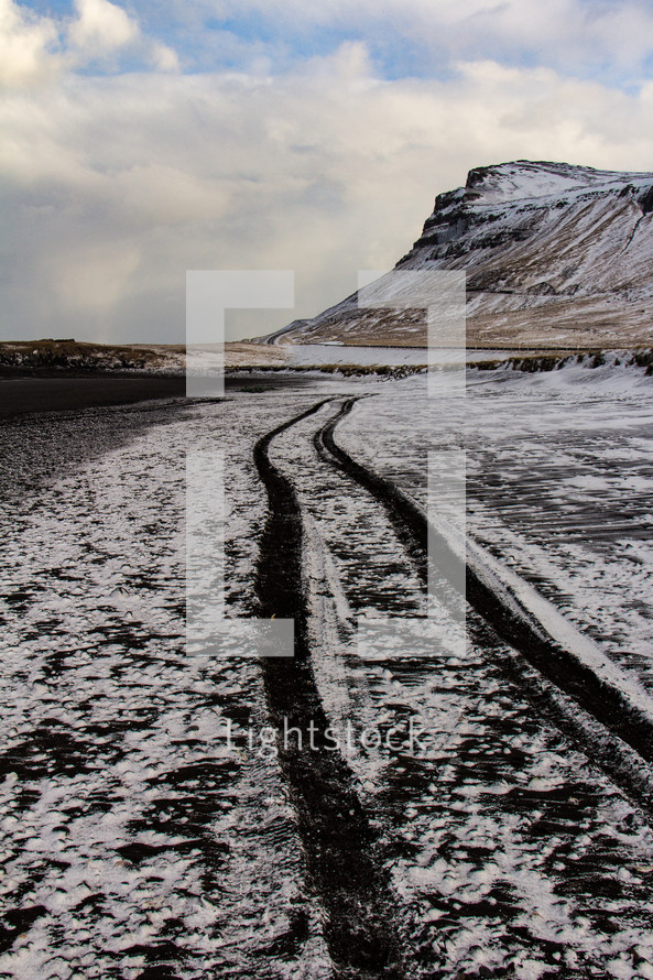 Snow covered black sand beach on the Snaefellsnes peninsula in Iceland with tire tracks leading into the distance toward a cliff.