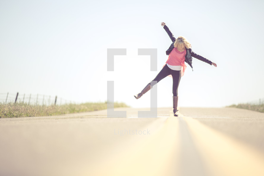 Woman balancing on one leg in the middle of the road.