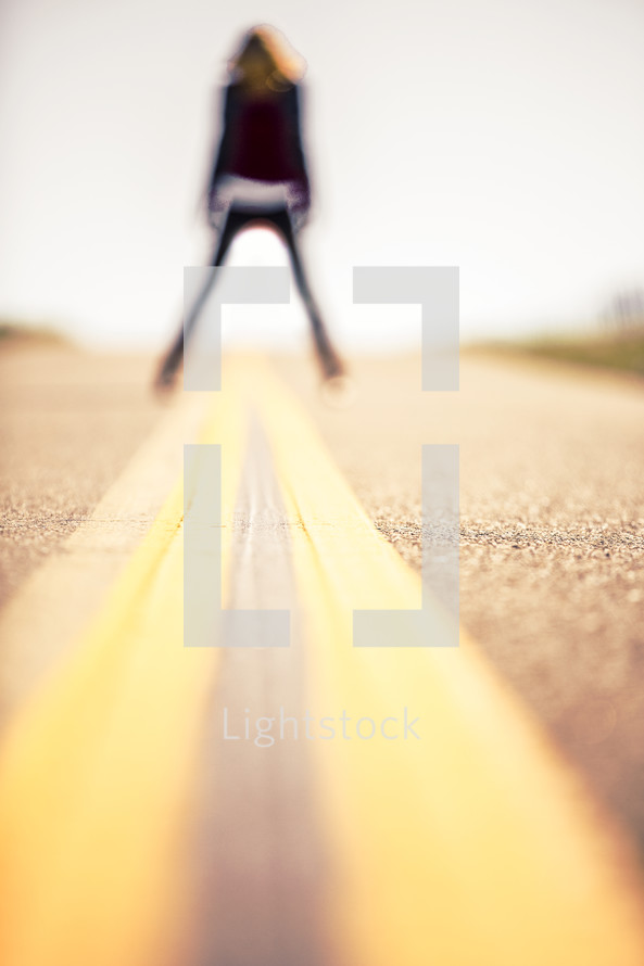 Woman straddling the stripe in the middle of the road.