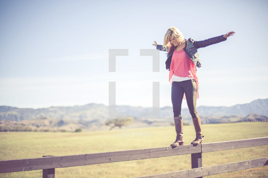 Woman balancing on a fence rail in a pasture with mountains.