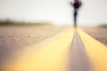 Woman walking down the middle of the road.