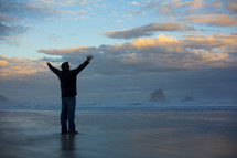 silhouette of a man with raised hands standing on a beach
