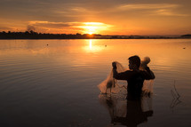 a man standing in a lake with a fishing net at sunset