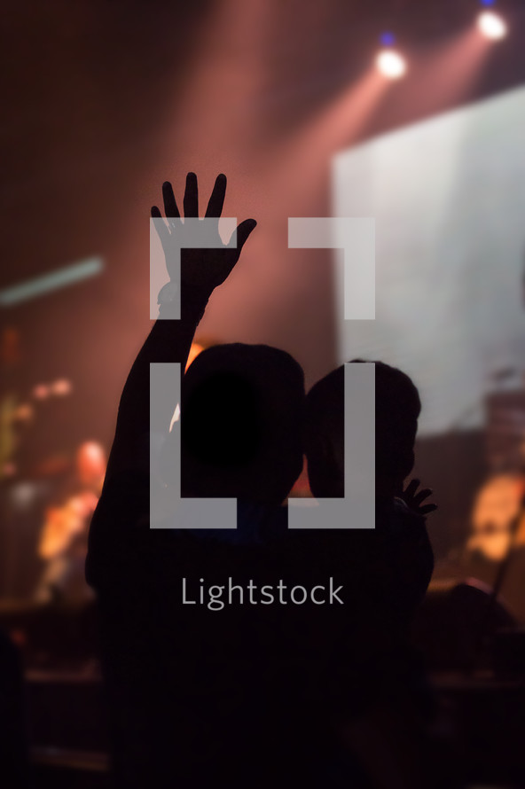 silhouette of a man holding a boy with a raised hand at a concert