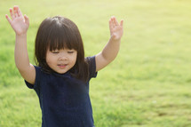 a child with raised hands and worship